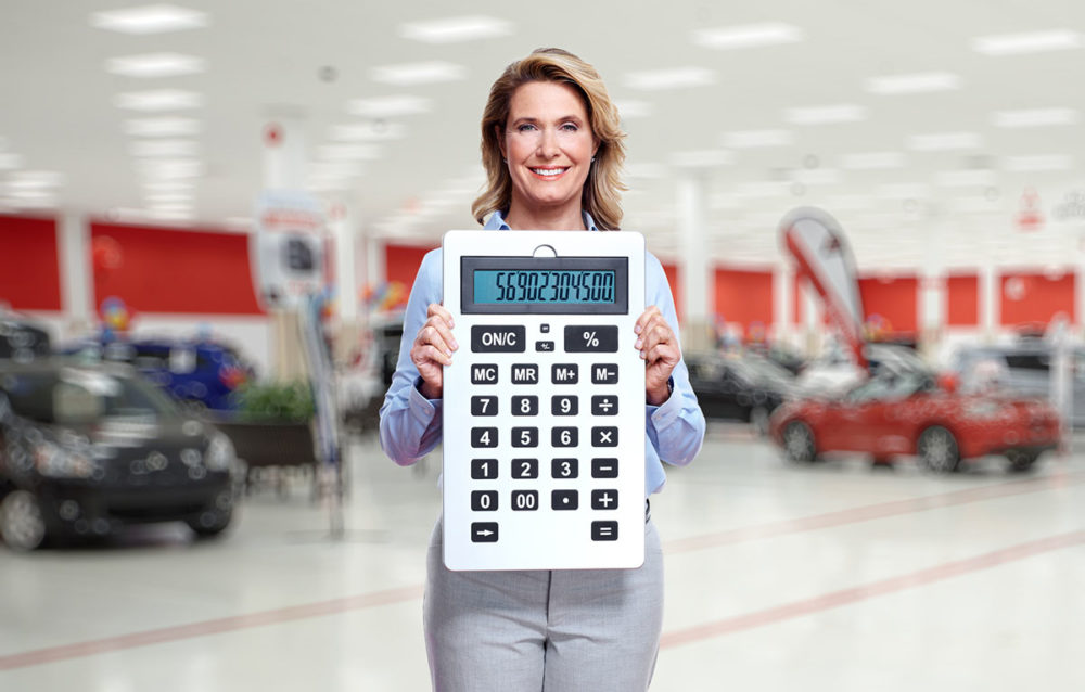 Woman in Car Shop Holding Calculator