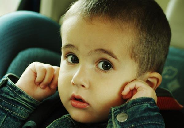 Boy stops up his ears with fingers avoiding loud sound of traffic in the car